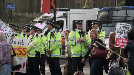 proti : A stationary shot of a group of policemen chatting and standing close to protesters near Hungerford Bridge, London. Also, there are some policecars parked nearby. The protestors are against the government cutting their healthcare coverage. In this scene,  Dostupné videozáznamy