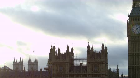 парламент : A panning view of the uppermost part of Westminster Palace in London. The camera starts sliding from left to right and finally stops on Big Ben clock tower. The tme is 5:36 PM. There are some clouds on the sky otherwise it is rather clear. Filmed on Octob Стоковые видеозаписи