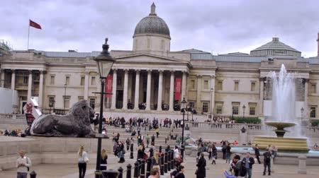 kolumna : Stationary view of Trafalgar Square, shows brass lion statues, unidentified people, and fountain in background, red bus passes camera in foreground in London, England. Filmed on October 11, 2011.