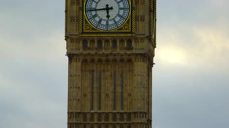 történelmi : Starting from the very tip of it the camera gradually moves downwards on Big Ben clock tower in London. It finally reaches the street level where some trees can be seen. Filmed on a slightly cloudy day October 9 2011.