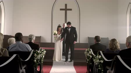 padre : Dolly shot going up the aisle of a chapel as a newlywed couple kisses turns to face the guests and walks back down the aisle as the audience applauds. Light streams in from the windows. Stock Footage
