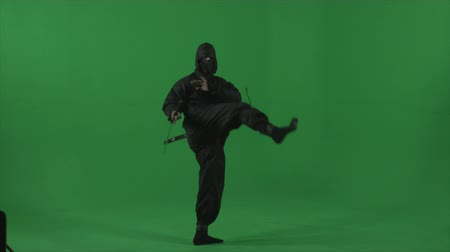 deneyimli : Ninja flourishes his sword and performs kicks and flips expertly in front of studio green screen.