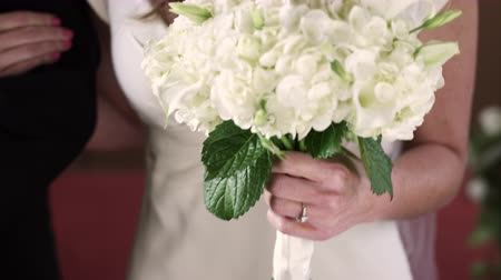 lét : Close-up follow dolly shot in front of a bride being escorted by her father down the aisle of a church at her wedding ceremony. The shot is on the brides wedding ring and bouquet as she walks down the aisle. Stock mozgókép