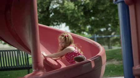 apu : Slow motion of red headed girl coming down slide and smiling.