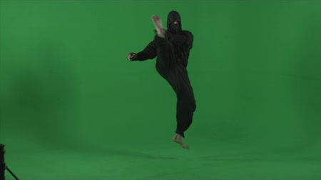 samuraj : Ninja dressed in black does barefooted round house kicks. Shot in studio against a green screen in slow motion