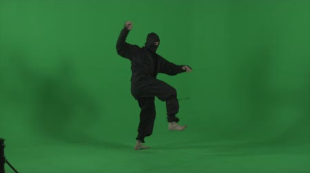 samuraj : Ninja dressed in black does round house high kicks barefooted. Shot in studio against a green screen in slow motion Wideo