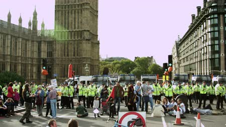 proti : A stationary shot of policemen and policecars forming a row to block protesters near Big Ben. The demonstrators are against the government cutting their healthcare coverage. Filmed on October 9, 2011. Dostupné videozáznamy