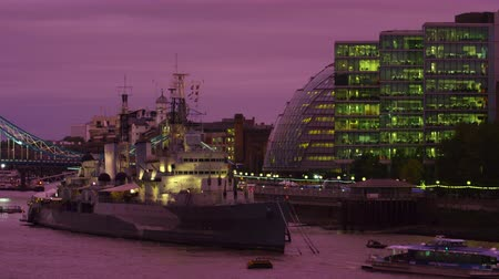 ancorado : A stationary shot of a ship anchored close to London city hall. A boat passes it. It is early evening and it is darkening outside. A glimpse of Tower Bridge also seen. Filmed on October 10 2011.