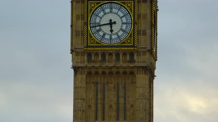 inferior : Starting from the street level the camera moves up on Big Ben clock tower in London finally stopping on the number dial. The time is 5:43 PM. Cloudy sky surrounds the tower and in the bottom some trees can be seen. Filmed on October 9 2011.