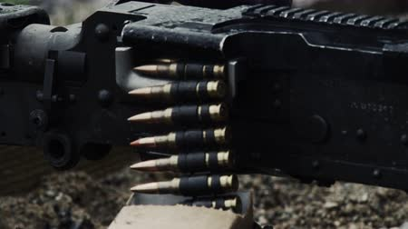 стрельба : Shot of a belt-fed machine gun as it is fired. Close-up on where the chain of rounds goes through the gun. Smoke comes from the gun as it is shot. From a training for Green Beret United States Army Special Forces.