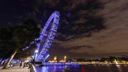 Лондон : Wide angle time-lapse at night of the London Eye Ferris Wheel with Big Ben and the Houses of Parliament in the distant background. The purplish light from the London Eye is reflected in the River Thames. Filmed in October 2011 Стоковые видеозаписи