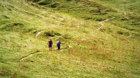 hiking : static shot of two hikers walking downa winding path in a green grassy meadow