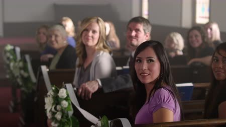 mech : People turning around and smiling as a bride walks down the aisle of a chapel. Filmed from the point of view of the bride.