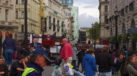 londyn : Shot from Piccadilly Circus in London looking down Coventry Street. People are sitting on the steps of the Shaftesbury Monument Memorial Fountain and walking through the plaza. Ripleys Believe It Or Not and the Criterion Theater can be seen as well. Shot Wideo