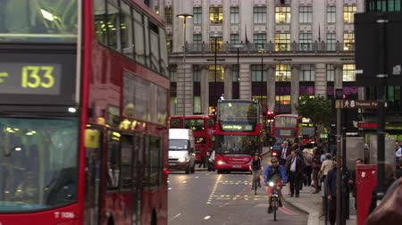 dvojitý : Panning view from left to right of a bustling street in London. At the end of the workday cabs double-deckers cars cyclists and crowds of people can be seen on the street. Filmed on an overcast day October 10 2011.