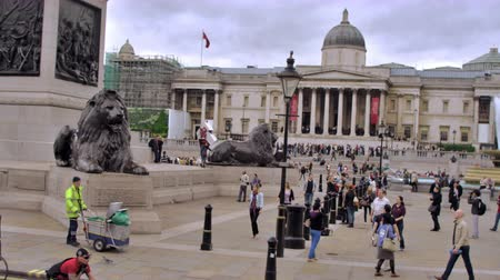kolumna : Slow motion stationary view of unidentified people near the Brass lion statues in Trafalgar Square, cars pass camera in foreground in London England. Filmed on October 11, 2011.