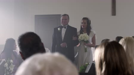 mech : Follow dolly shot in front of a father escorting his daughter down the aisle of a church at her wedding ceremony. The bride looks around and seems hesitant uncertain or just serious. Beautiful lighting streaming from the windows.
