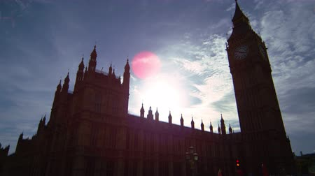 Лондон : The camera slides from left to right, showing Big Ben clock tower on a sunny, glistening afternoon. The dazzling sun creates and interesting light effect in the sky. Filmed on October 9, 2011. Стоковые видеозаписи