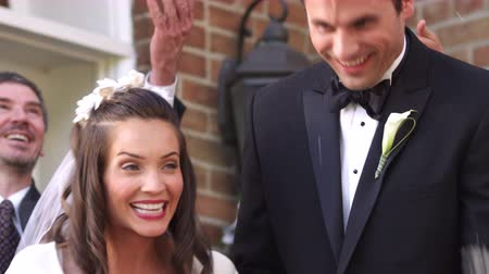 nevěsta : Slow-motion shot of a bride and groom walking out of a church door and down steps smiling as guests throw rice above them and applaud.