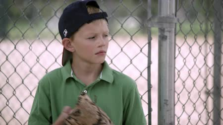 beisebol : Slow motion of boy looking to the side as he hits his baseball mitt. Stock Footage