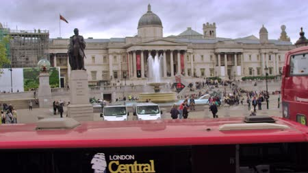 kolumna : Panning view of numerous red buses in front of Trafalgar Square. Unidentified people, fountain, brass lion statues, and museum in background, camera pans to the left ending on a street full of cars in London England. Filmed on October 11, 2011.