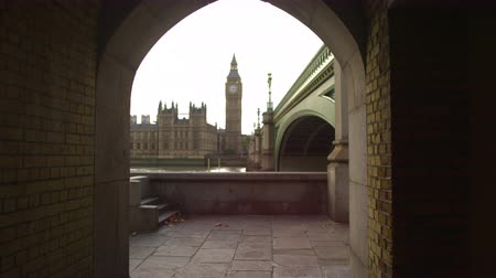 парламент : A stationary shot of Westminster Palace and Big Ben clock tower in London. The shot is filmed from a tunnel next to Westminster Bridge which is across river Thames. Filmed on October 9 2011. Стоковые видеозаписи