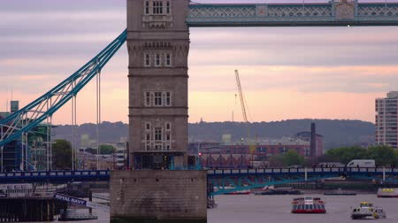 történelmi : A stationary shot of Tower Bridger over river Thames in London. Boats are passing under it and cars driving over it. Filmed on an overcast autumn day October 10 2011.