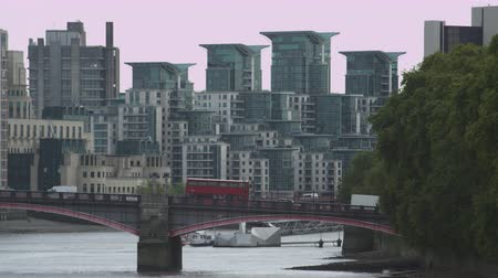 estrutura residencial : A stationary shot of cars and buses passing over Lambeth Bridge in London. There are modern buildings in the background and a boat on the river Thames. Filmed on October 9 2011.