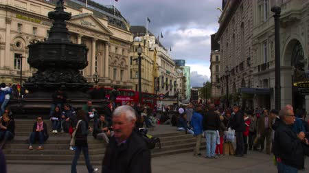 dvojitý : Shot of Piccadilly Circus in London. People are sitting on the steps of the Shaftesbury Monument Memorial Fountain and walking through the plaza. Ripleys Believe It Or Not and the Criterion Theater can be seen as well. Shot on October 7 2011.