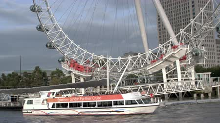 kör alakú : Panning view of boat in front of the London eye in London, England. Filmed on October 11, 2011. Stock mozgókép