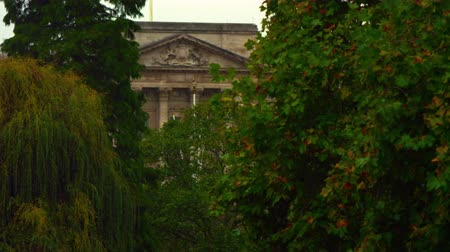 buckingham palace : A stationary shot of a part of the Buckingham Palace, framed with green branches of trees in Saint James Park, London. Filmed on October 8, 2011.