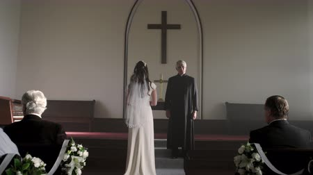 padre : Dolly out showing a bride at the front of a chapel in front of a preacher with no groom. The preacher slightly shakes his head as he looks around. Light is streaming through the windows. Stock Footage
