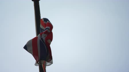 império : A stationary close-up shot of British flag, attached to a flagpole, flapping in the wind. Surrounded by blue sky. Filmed during daytime on October 9, 2011.