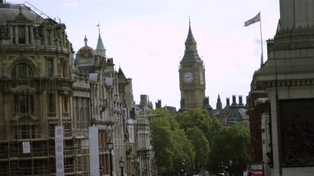 Лондон : A stationary view of Big Ben clock tower in London, filmed from the base of Lord Nelsons monument, which is located on Trafalgar square. Some buildings, trees, sky, and a waving British flag also visible. Filmed on October 9, 2011.