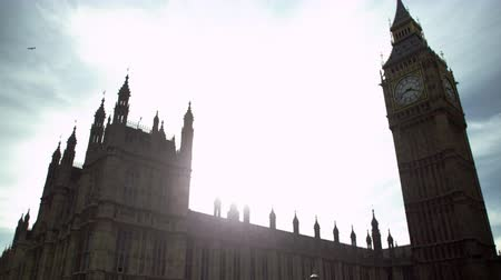 esquerda : The camera pans slightly from left to right, focusing on Big Ben clock tower in London. Taken in the afternoon, the sun is dazzling, creating an interesting light effect. Filmed on October 9, 2011. Stock Footage