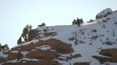 prędkość : Slow motion shot of a man is skiing down a snowy mountain path he comes to the edge and base jumps off. He balances then curls into a somersault. The clip ends as he pulls his chute.