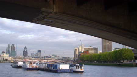 парламент : Camera travels under Waterloo Bridge, shows boats on River Thames with buildings in background in London, England. Filmed on October 11, 2011.