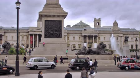 bronz : Stationary view of street in front of Trafalgar Square, unidentified people walk around and cars drive on street passing the brass lion statues and fountain in London, England. Filmed on October 11, 2011.