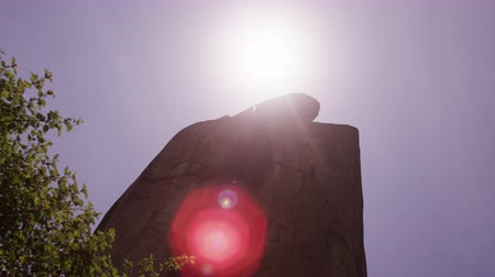 diretamente : Low angle pan of enormous rock, Filmed near its base. The sun is directly above the rock, creating lens flare. Filmed in Kenya, Africa. Stock Footage