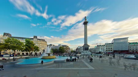 еще : Time-lapse of Trafalgar Square in London. People walk around the fountains and Nelsons Column. There is a cloudy yet blue sky overhead. Filmed in October 2011.