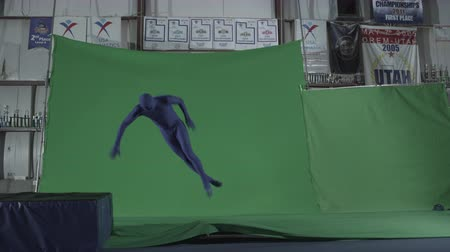colchão : Slow motion green screen shot of man in blue full body suit performing stunt by jumping on the springboard and diving into an air mattress