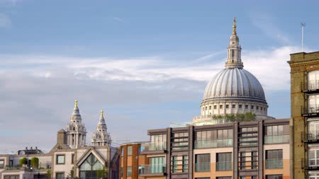 londyn : Traveling view of buildings in front of St. Pauls Cathedral shows the steeples and dome in the background in London England. Filmed on October 11 2011.