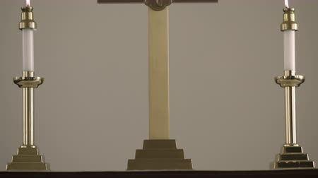 padre : Tilt shot showing an altar with two candles and a gold crucifix in a church. Stock Footage