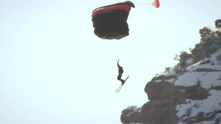jumped : A base jumper appears to have just jumped off the rocky ledge. He is headed left then makes a right turn as the mountains come into view behind him. This is shot in slow motion.