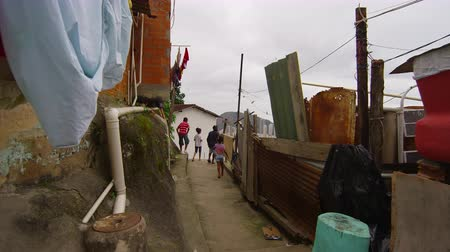indigence : Slow motion dolly shot of children walking in a favela in Rio de Janeiro, Brazil taken with a high speed camera. Stock Footage