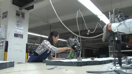 southeast : Garment factory workers cutting fabric for production using electric bandsaws