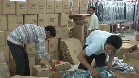 clothing : Garment factory workers pack completed garments into boxes for shipping, with stack of boxes behind them Stock Footage