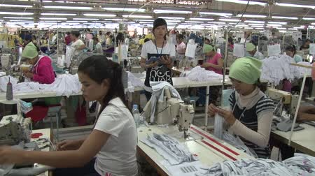 kumaş : Seated garment workers preparing garments and sewing while monitor observes them; factory action in background