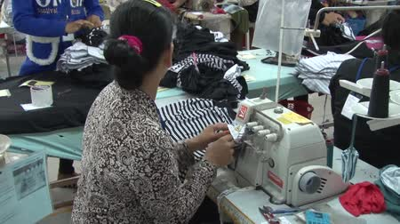 southeast : unidentified seated female garment worker sewing striped fabric pieces with a heavy sewing machine Stock Footage