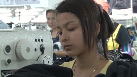 southeast : Female garment worker operating heavy industrial sewing machine with other workers in background